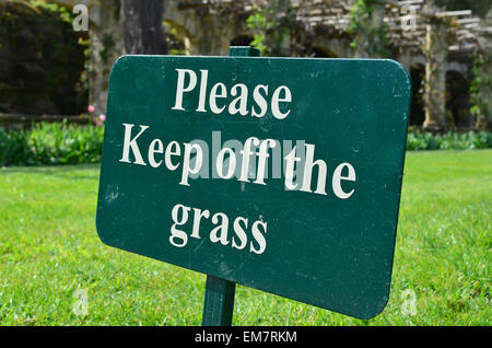 Please keep off the grass sign on a  freshly mowed lawn in England - Stock Photo