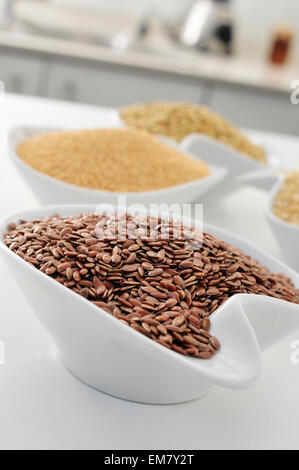 closeup of a bowl with brown flax seeds, and other seeds and cereal in the background, on the countertop of a kitchen - Stock Photo