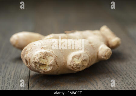 big piece of ginger root on wooden table - Stock Photo