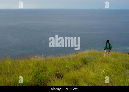 Female traveler walks at Tanjung Kajuwulu, Maumere, Flores Island, Indonesia. - Stock Photo