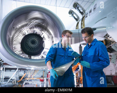 Engineers inspecting jet engine turbine blade in aircraft maintenance factory - Stock Photo