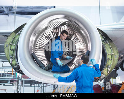 Engineers working with jet engine turbine blade in aircraft maintenance factory - Stock Photo