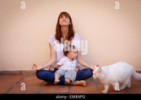 Portrait of mid adult woman practicing yoga with baby daughter on kitchen floor - Stock Photo