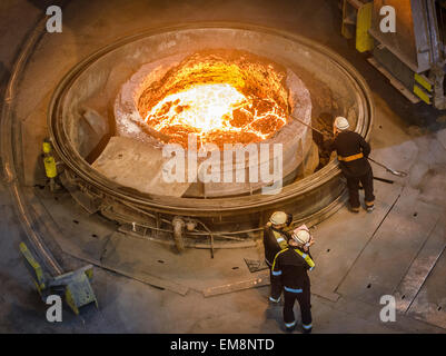 Steel workers inspecting molten steel in flask, high angle view - Stock Photo