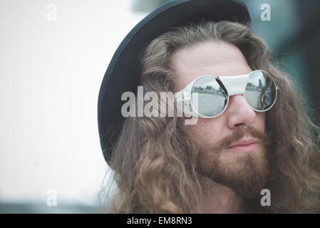 Close up of young male hippy with long hair and sunglasses - Stock Photo