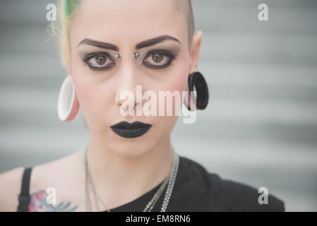 Portrait of young female punk with nose and earlobe piercings - Stock Photo