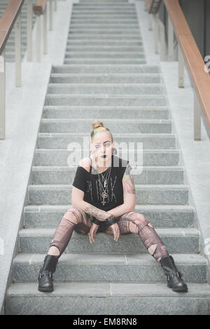Portrait of young female punk sitting on subway staircase - Stock Photo