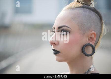 Portrait of young female punk with earlobe piercing and shaved head - Stock Photo