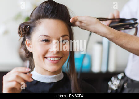 happy woman with stylist making hairdo at salon - Stock Photo