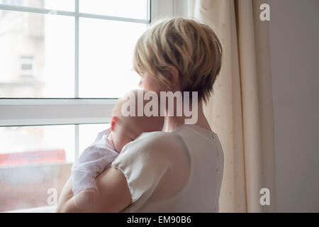 Mother carrying sleeping baby girl, looking out window - Stock Photo