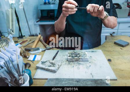 Cropped shot of jewellery craftsman filing platinum ring - Stock Photo