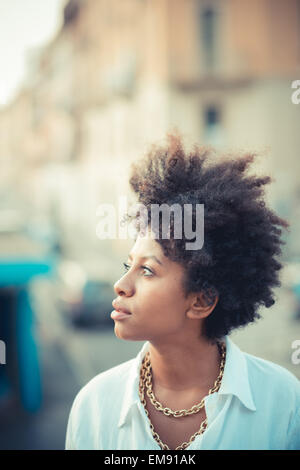 Portrait of beautiful young woman gazing in city - Stock Photo