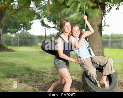 Teenage girl pushing her sister on tire swing - Stock Photo