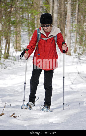 A woman out for a hike in the winter snow with her snowshoes and poles. - Stock Photo