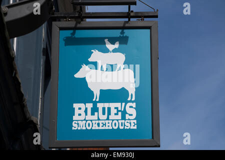 hanging sign for a branch of the barbecued food restaurant, blue's smokehouse, twickenham, middlesex, england - Stock Photo