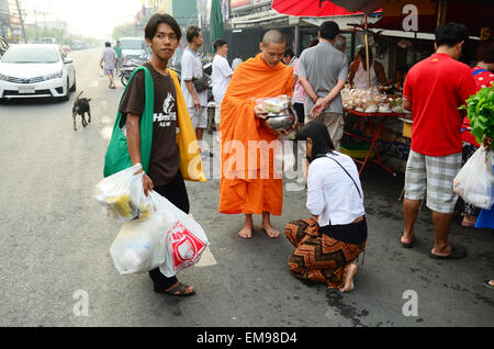 People put food offerings in a Buddhist alms bowl at Bangyai small market on April 12, 2015 in Nonthaburi Thailand - Stock Photo