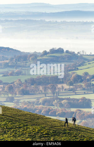 Two people walking over Sugarloaf Hill on Malvern HIlls with Hereford valley in mist in the background - Stock Photo