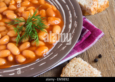 Beans in tomato sause with dill on wooden background, close up horizontal - Stock Photo