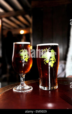 Pint glass and half pint glass with Harveys Best Bitter beer served at the John Harvey Tavern in Lewes - Stock Photo