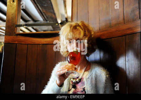 Woman drinking half pint glass of Harveys best bitter beer at the John Harvey Tavern pub in Lewes East Sussex UK - Stock Photo