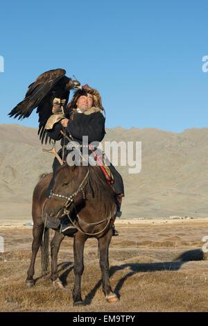 Elder Kazakh eagle hunter posing with his eagle and his horse #3, Western Mongolia - Stock Photo