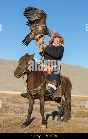 Elder Kazakh eagle hunter posing with his eagle and his horse #2, Western Mongolia - Stock Photo