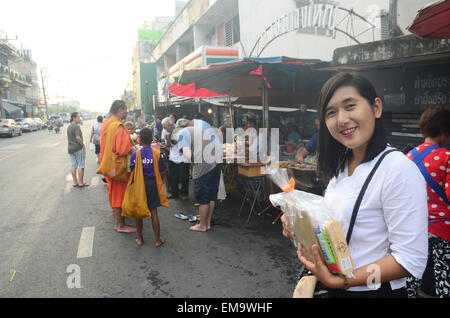 People put food offerings in a Buddhist alms bowl at Bangyai small market on April 12, 2015 in Nonthaburi Thailand. - Stock Photo