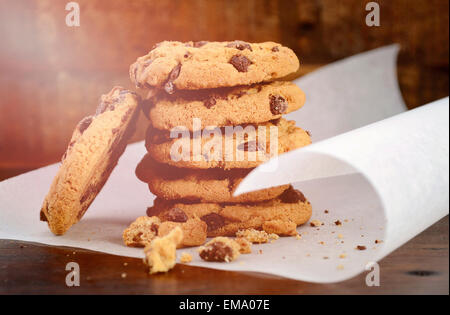 Stack of chocolate chip cookies on white curling baking paper against a dark wood background, with applied vintage - Stock Photo