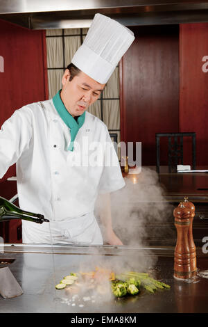 Cook pours sauce on meal - Stock Photo