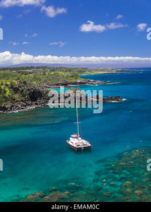 Snorkelers and tour boat Hula Girl in Honolua Bay, with Kapalua in distance - Stock Photo