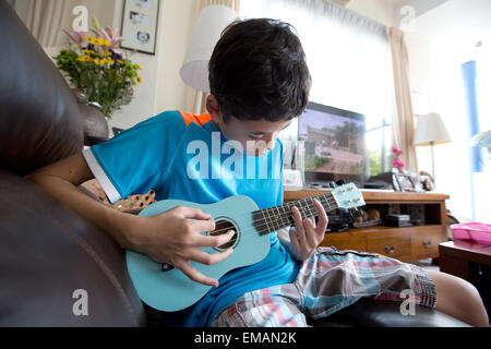 Young boy practicing on his ukulele - Stock Photo