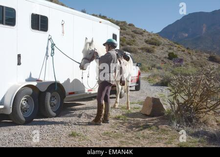 Putting on my horse's bridle for a ride in the mountains;  New Mexico - USA - Stock Photo