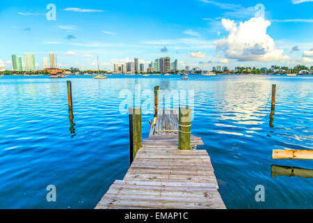 old wooden pier with view to modern skyline of Miami under blue sky - Stock Photo