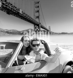 selfie of young teen couple at convertible car in San Francisco Golden Gate Bridge photo mount - Stock Photo