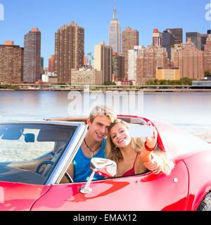 selfie of young teen couple at convertible car in New York Manhattan skyline photo mount - Stock Photo