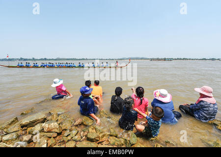 Chiang Saen, Thailand. 18th Apr, 2015. People sit on the bank of the Mekong River as they watch a boat race held - Stock Photo