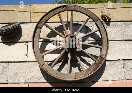 Old wooden wheel hanging on the stone wall in the garden - Stock Photo