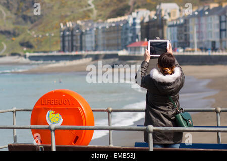 Aberystwyth, Wales, UK 19 April 2015 . A woman photographing a sunny seafront at Aberystwyth with a tablet computer - Stock Photo