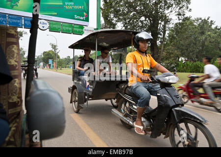 Western tourist couple in tuk-tuk on sightseeing tour in Siem Reap, Cambodia - Stock Photo