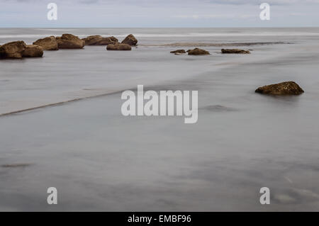 Slow shutter speed blurs water of the sea in Whitby, North Yorkshire, England. On 18th April 2015. - Stock Photo