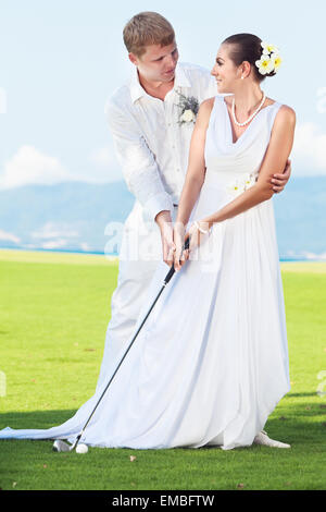 Bride and groom are playing golf at wedding day - Stock Photo