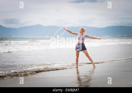 Young woman playing with hoola hoop ring at a beach on the Pacific coast of Mexico. - Stock Photo