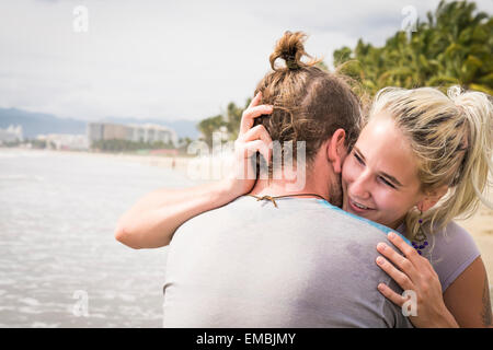 Young woman hugging young man, smiling, at a beach. Riviera Nayarit, Pacific Coast, Mexico
