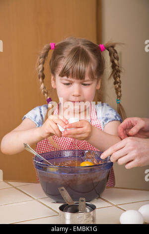 Five year old girl breaking an egg into a mixing bowl to become a chocolate bundt cake later, with dismay at the - Stock Photo