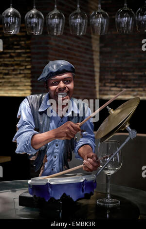 Wine bar advertising with a statue of an African-American man playing the drums set amidst wine glasses. - Stock Photo