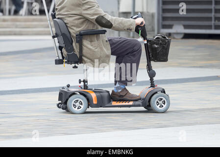 Cruise ship passenger using mobility scooter supplied by ship. - Stock Photo
