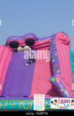 Giant Deflating Slide with a little girl sitting on it - Stock Photo