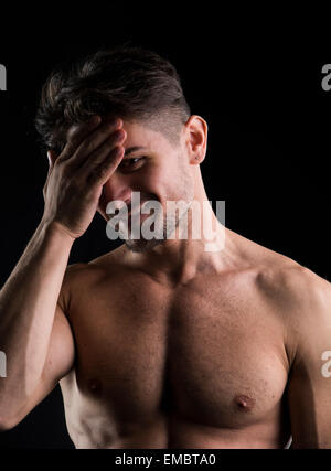 Muscular shirtless young man portrait isolated on black background - Stock Photo