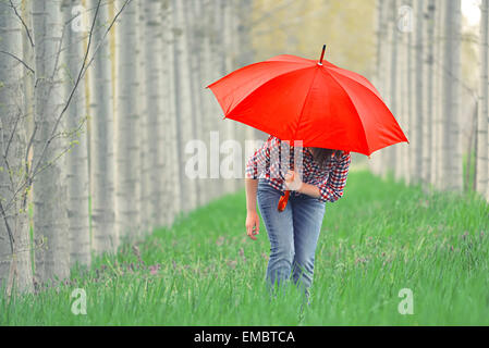 Woman with Red Umbrella In Tree Alley on Cloudy Afternoon - Stock Photo