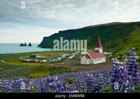 View over Vik (vik i myrdal) with its church and the reynisdrangar (basalt sea stacks) at dawn, South Iceland - Stock Photo
